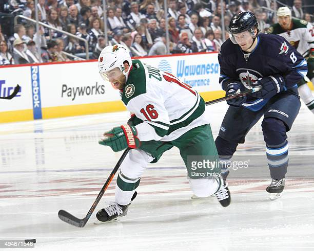 Jason Zucker of the Minnesota Wild plays the puck down the ice as Jacob Trouba of the Winnipeg Jets gives chase during third period action at the MTS...
