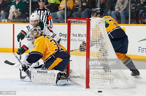 Jason Zucker of the Minnesota Wild shoots wide of the net against Marek Mazanec of the Nashville Predators at Bridgestone Arena on January 12 2014 in...
