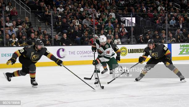 Jason Zucker of the Minnesota Wild skates with the puck against Alex Tuch and Nate Schmidt of the Vegas Golden Knights in the third period of their...