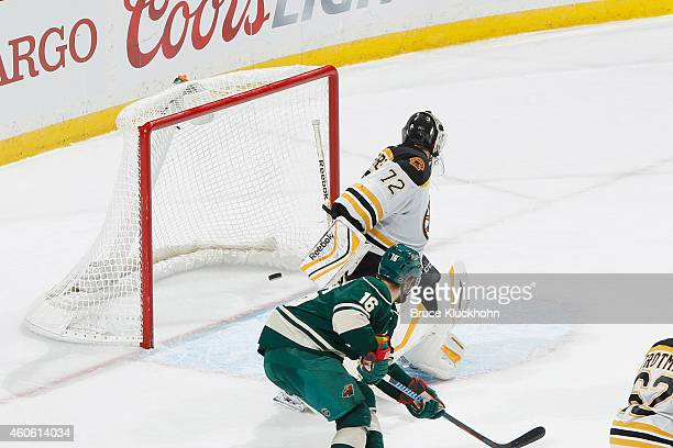 Jason Zucker watches as his Minnesota Wild teammate Jason Pominville scores a goal against Niklas Svedberg of the Boston Bruins during the game on...
