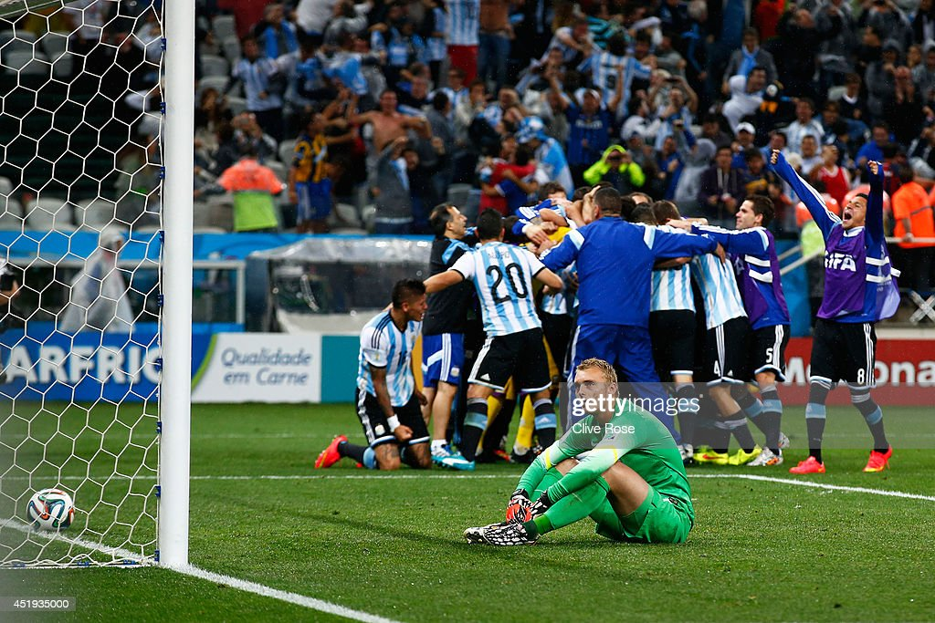 Jasper Cillessen of the Netherlands sits on the pitch after failing to save the penalty kick of Maxi Rodriguez of Argentina as Argentina celebrate during the 2014 FIFA World Cup Brazil Semi Final match between the Netherlands and Argentina at Arena de Sao Paulo on July 9, 2014 in Sao Paulo, Brazil.