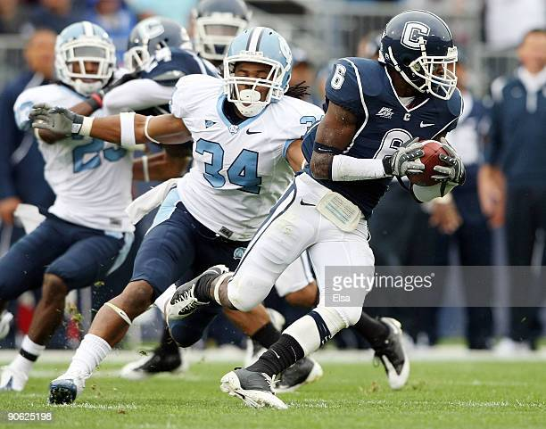 Jasper Howard of the Connecticut Huskies carries the ball as Johnny White of the North Carolinia Tar Heels tries to make the tackle on September 12...