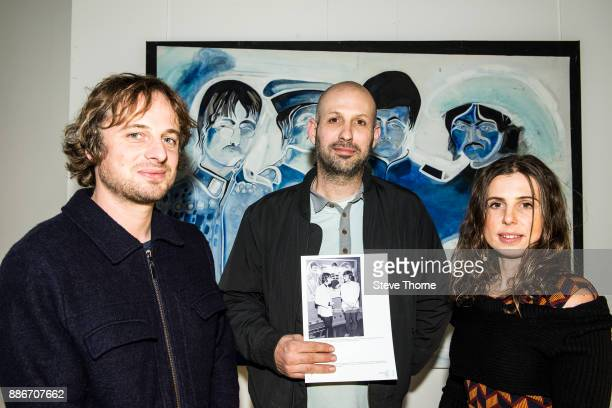 Jasper Josh and Eliza May sons and daughter of the late Jonathan Hague pose with one of their father's paintings of the Beatles at the opening of the...