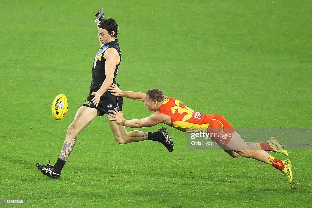 Jasper Pittard of the Power kick while tackled by Brandon Matera of the Suns during the round 22 AFL match between the Gold Coast Suns and the Port Adelaide Power at Metricon Stadium on August 29, 2015 in Gold Coast, Australia.