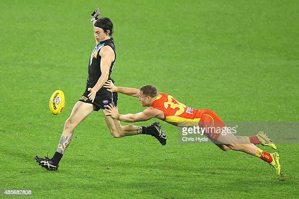 Jasper Pittard of the Power kick while tackled by Brandon Matera of the Suns during the round 22 AFL match between the Gold Coast Suns and the Port...