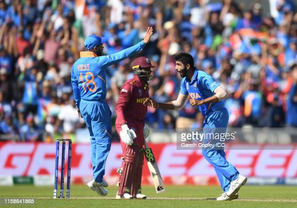 Jasprit Bumbrah of India celebrates after taking the wicket of Fabian Allen of West Indies with Virat Kohli of India during the Group Stage match of...