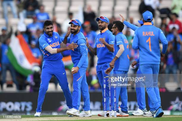 Jasprit Bumrah and Virat Kohli of India celebrate the wicket of Quinton De Kock of South Africa with their teammates during the Group Stage match of...