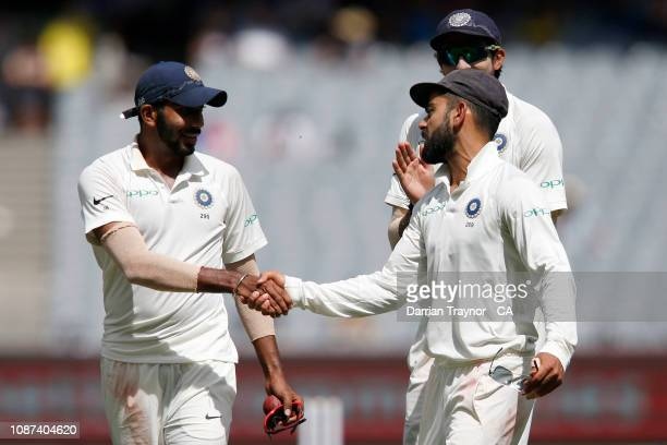 Jasprit Bumrah is congratulated by his captain Virat Kohli of India after he took six wickets in the Australian innings during day three of the Third...