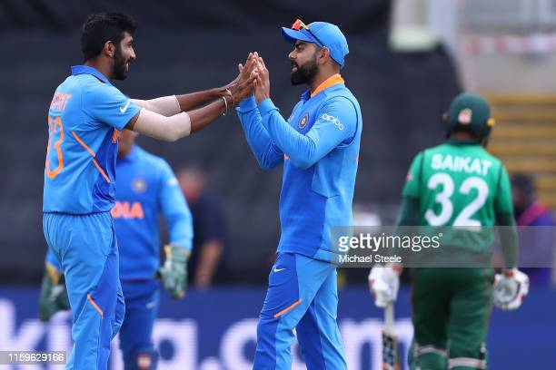 Jasprit Bumrah of India celebrates with captain Virat Kohli after taking the wicket of Mosaddek Hossain during the Group Stage match of the ICC...