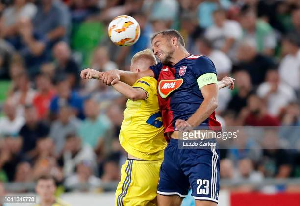Jasse Tuominen of FC BATE Borsiov battles for the ball in the air with Roland Juhasz of Vidi FC during the UEFA Europa League Group Stage match...