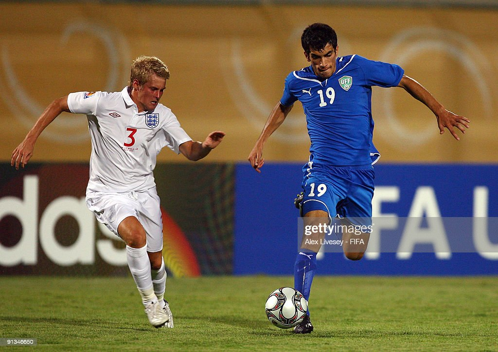 Jasur Khasanov of Uzbekistan takes on Jordan Parkes of England during the FIFA U20 World Cup Group D match between Uzbekistan and England at the Mubarak Stadium on October 2, 2009 in Suez, Egypt.