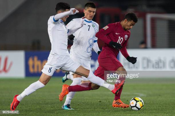 Jasurbek Yakhshiboev of Uzbekistan and Akram Afif of Qatar in action during the AFC U23 Championship Group A match between Qatar and Uzbekistan at...