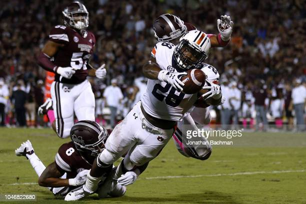 JaTarvious Whitlow of the Auburn Tigers fumbles the ball as Mark McLaurin and Maurice Smitherman of the Mississippi State Bulldogs defend during the...