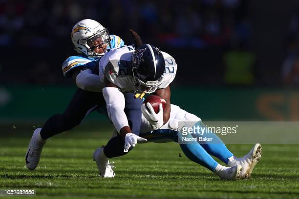 Jatavis Brown of Los Angeles Chargers brings down Derrick Henry of Tennessee Titans during the NFL International Series match between Tennessee...