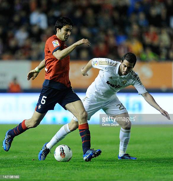 Javad Nekounam of CA Osasuna is tackled by Gonzalo Higuain of Real Madrid CF during the La Liga match between CA Osasuna and Real Madrid CF at...