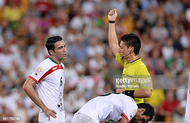 Javad Nekounam of Iran is given a yellow card by referee Ryuji Sato during the 2015 Asian Cup match between IR Iran and the UAE at Suncorp Stadium on...