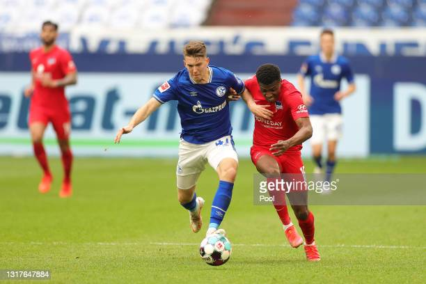 Javairo Dilrosun of Hertha BSC is challenged by Florian Flick of FC Schalke 04 during the Bundesliga match between FC Schalke 04 and Hertha BSC at...