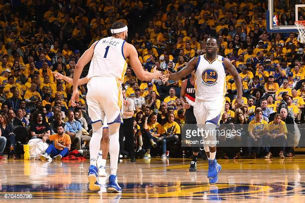 JaVale McGee and Draymond Green of the Golden State Warriors high five each other during the game against the Portland Trail Blazers during Game Two...