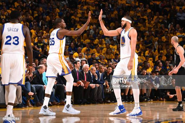 JaVale McGee and Kevin Durant of the Golden State Warriors high five each other during the game against the San Antonio Spurs during Game Two of the...