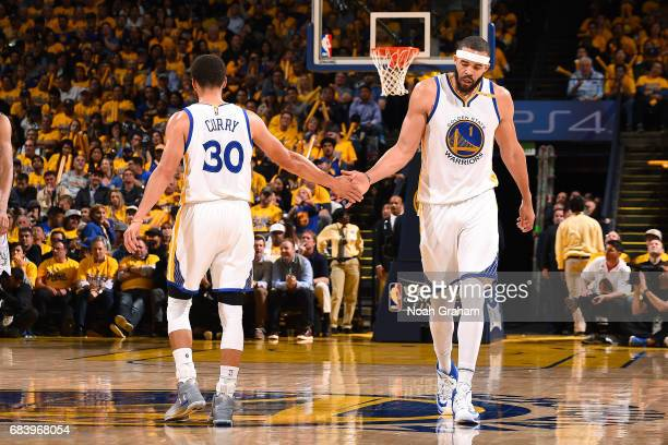 JaVale McGee and Stephen Curry of the Golden State Warriors high five each other during the game against the San Antonio Spurs during Game Two of the...