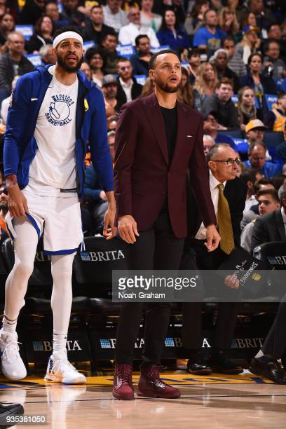 JaVale McGee and Stephen Curry of the Golden State Warriors looks on during the game against the Sacramento Kings on March 16 2018 at ORACLE Arena in...