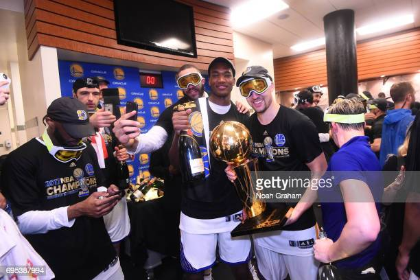JaVale McGee Damian Jones and Klay Thompson of the Golden State Warriors celebrates in the locker room after defeating the Cleveland Cavaliers in...