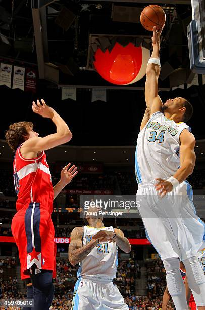JaVale McGee of the Denver Nuggets blocks a shot by Jan Vesely of the Washington Wizards at the Pepsi Center on January 18 2013 in Denver Colorado...