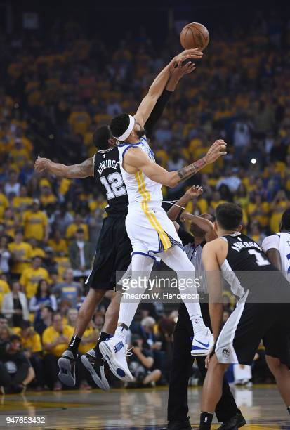 JaVale McGee of the Golden State Warriors and LaMarcus Aldridge of the San Antonio Spurs battles for the tipoff of Game One of the first round of the...