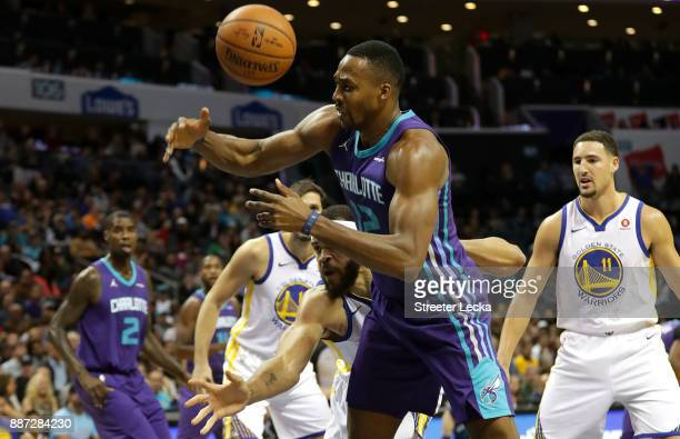 JaVale McGee of the Golden State Warriors battles for a loose ball against Dwight Howard of the Charlotte Hornets during their game at Spectrum...