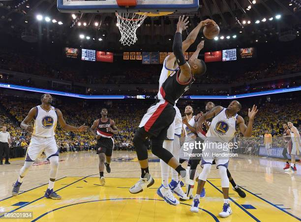 JaVale McGee of the Golden State Warriors blocks the shot of Damian Lillard of the Portland Trail Blazers in the third quarter during Game One of the...