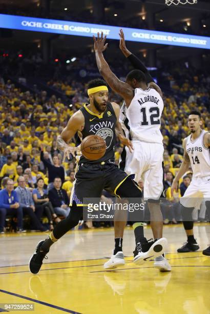 JaVale McGee of the Golden State Warriors dribbles around LaMarcus Aldridge of the San Antonio Spurs during Game 2 of Round 1 of the 2018 NBA...