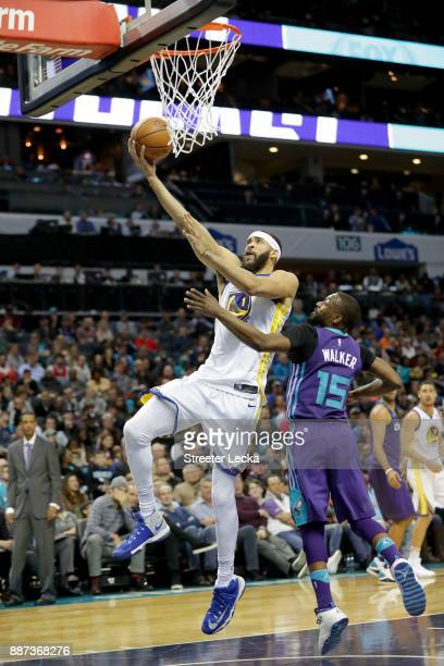 JaVale McGee of the Golden State Warriors drives to the basket against Kemba Walker of the Charlotte Hornets during their game at Spectrum Center on...