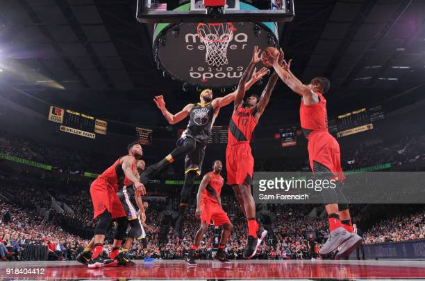 JaVale McGee of the Golden State Warriors Ed Davis and Damian Lillard of the Portland Trail Blazers reach for the rebound during the game between the...