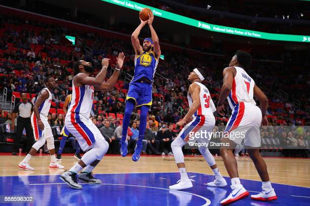 JaVale McGee of the Golden State Warriors takes a first half shot next to Andre Drummond of the Detroit Pistons at Little Caesars Arena on December 8...
