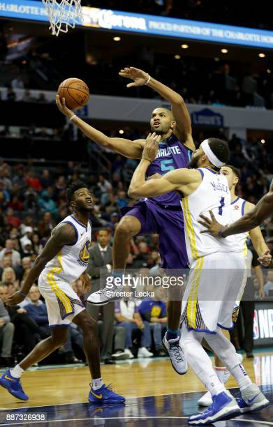 JaVale McGee of the Golden State Warriors watches as Nicolas Batum of the Charlotte Hornets drives to the basket during their game at Spectrum Center...