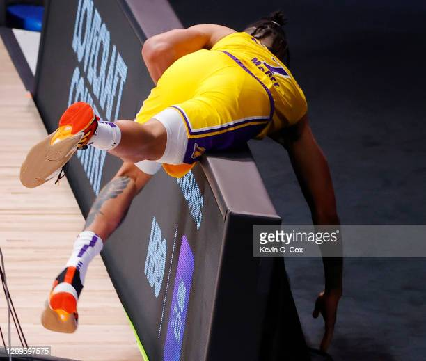 JaVale McGee of the Los Angeles Lakers jokes around and falls on the wall after drawing a foul from Carmelo Anthony of the Portland Trail Blazers...