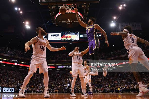 JaVale McGee of the Los Angeles Lakers slam dunks the ball over Aron Baynes of the Phoenix Suns during the second half of the NBA game at Talking...
