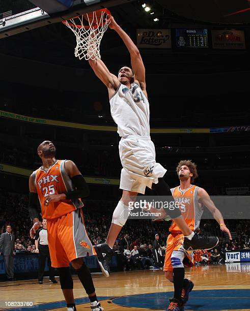 JaVale McGee of the Washington Wizards dunks against Vince Carter and Robin Lopez of the Phoenix Suns at the Verizon Center on January 21 2011 in...