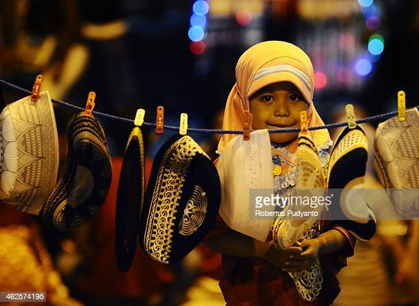 Javanese girl keeps on her skull cap merchandise at Sekaten festival on January 14 2014 in Solo City Indonesia Indonesia celebrates the birth of...