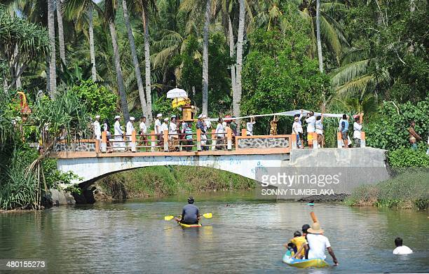 Javanese Hindus parade across a bridge before a Melasti ceremony prayer on Pulau Merah in Banyuwangi regency in East Java province on March 23 west...