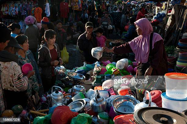 Javanese Muslim woman sells home ware at her stall in the Kintamani market Cheap homeware plastic and otherwise have been flooding into Bali from...