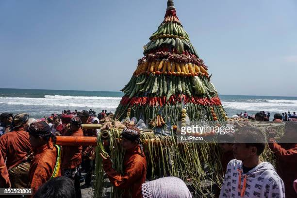 Javanese people carry an offerings during the ritual ceremony of labuhan 1st Suro during the Islamic New Year celebration at Goa Cemara beach in...