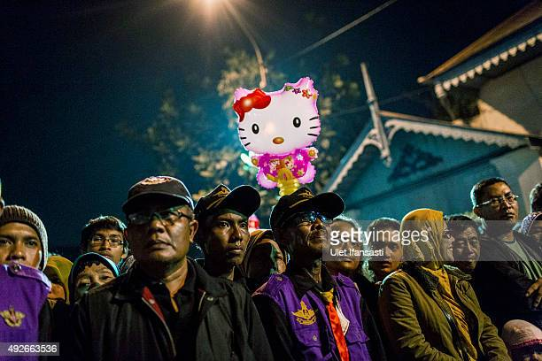 Javanese people stand while awaiting the traditional night carnival '1st Suro' marking the 1437th Islamic New Year celebrations at Kasunanan Palace...