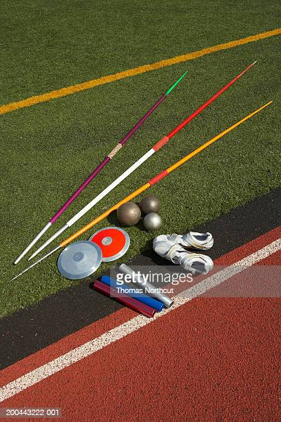 Javelins, discuses, relay batons, shots and sports shoes beside track