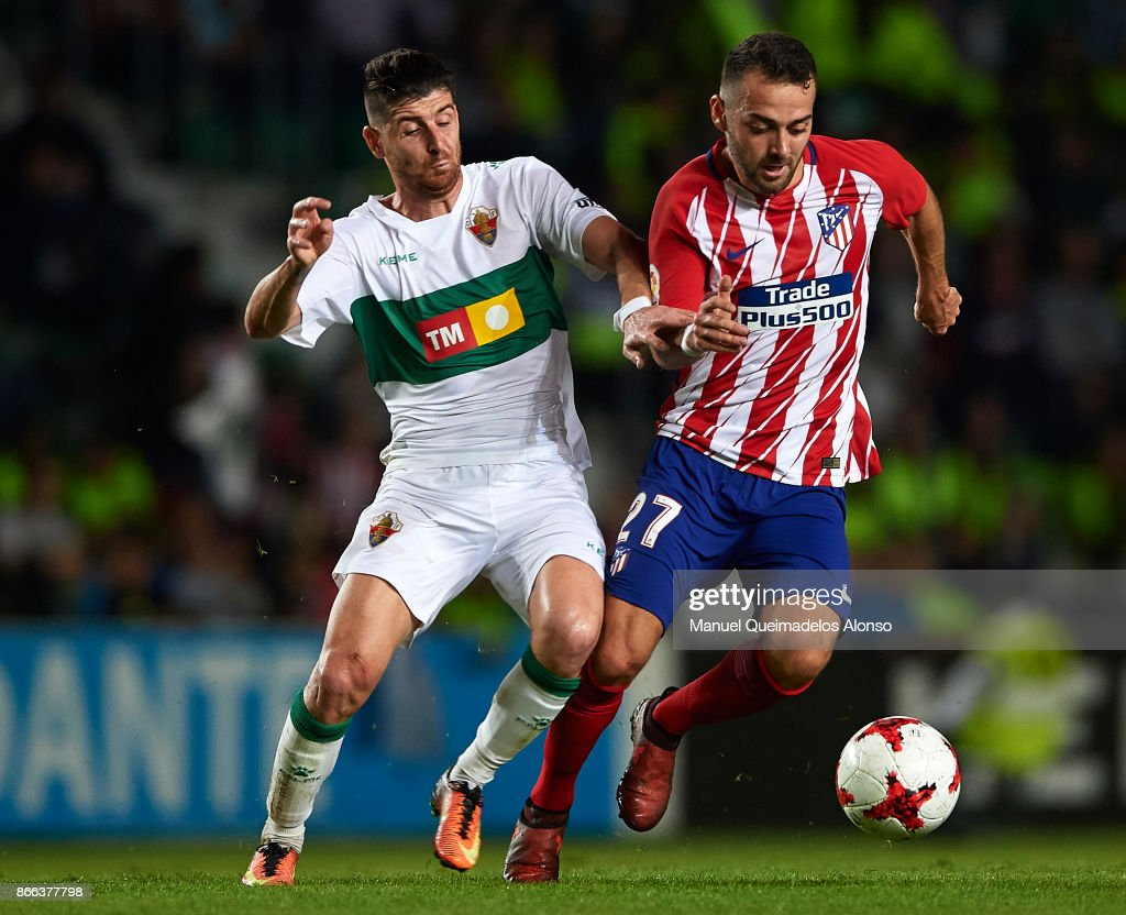 Javi Flores of Elche competes for the ball with Keidi Bare (R) of Atletico de Madrid during the Copa del Rey first leg match between Elche CF and Atletico de Madrid at Estadio Martinez Valero on October 25, 2017 in Elche, Spain.