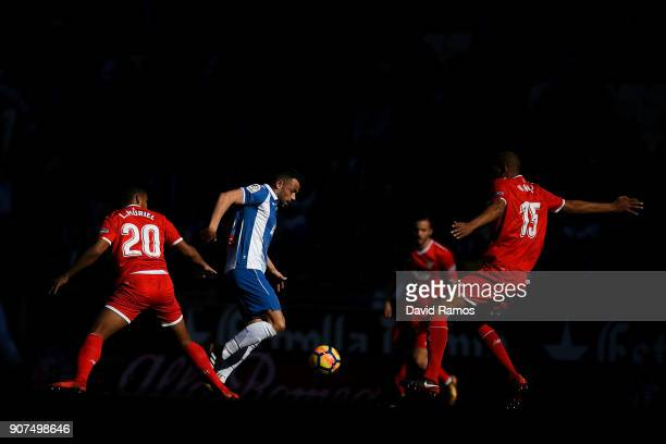 Javi Fuego of RCD Espanyol competes for the ball with Luis Muriel and Steven N'Zonzi of Sevilla FC during the La Liga match between Espanyol and...