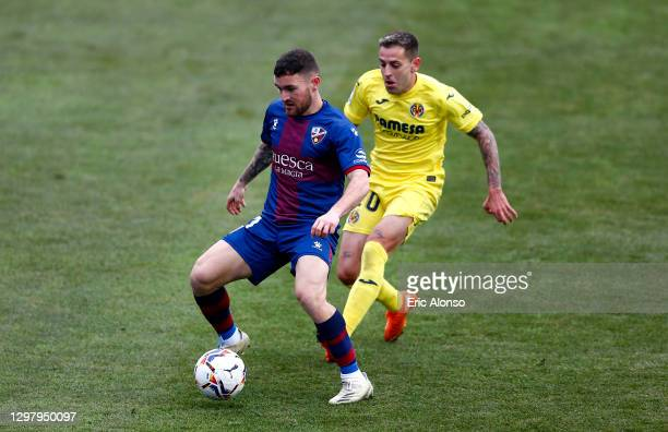 Javi Galan of SD Huesca is challenged by Ruben Pena of Villarreal CF during the La Liga Santander match between SD Huesca and Villarreal CF at...