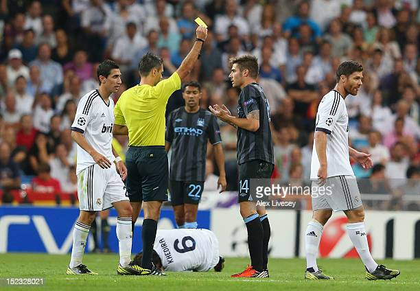 Javi Garcia of Manchester City FC is shown a yellow card during the UEFA Champions League Group D match between Real Madrid and Manchester City FC at...