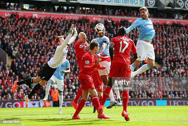 Javi Garcia of Manchester City heads at goal past the dive of Simon Mignolet of Liverpool during the Barclays Premier League match between Liverpool...