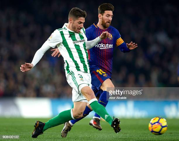 Javi Garcia of Real Betis Balompie being followed by Lionel Messi of FC Barcelona during the La Liga match between Real Betis and Barcelona at...